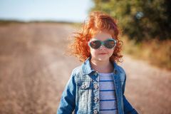 Portrait Cute little Red Curly girl in sunglasses Royalty Free Stock Photo