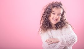 Portrait of a little curly girl on a pink background. Portrait of a cute little smiling curly girl on a pink background stock images