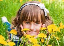 Portrait of a cute little smiling girl. Portrait of cute little smiling girl with big gray eyes among dandelions Stock Photo