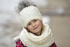 Portrait of cute little young funny pretty smiling blond child girl with gray eyes in nice warm winter clothing on white bright bl stock photo