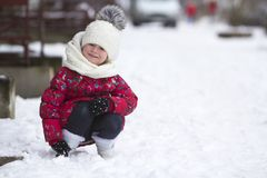 Portrait of cute little young funny smiling child girl in nice warm clothing playing in snow having fun on winter cold day on whit royalty free stock photography