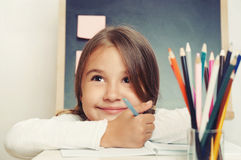 Portrait of cute lovely girl drawing in copybook on blackboard b Royalty Free Stock Images