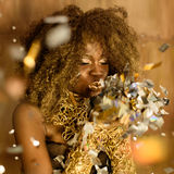 Portrait of cute lovely young woman blowing on small sparkling stars over gold background.  Royalty Free Stock Image