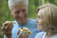 Portrait of cute mature couple eat pizza close-up royalty free stock photos