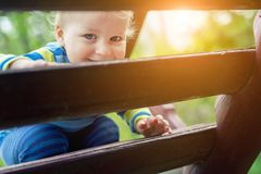 Portrait of cute mischievous caucasian blond baby boy holding wooden banister climbing staircase at outdoor backyard playground. stock photos