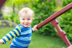 Portrait of cute mischievous caucasian blond baby boy holding wooden banister climbing staircase at outdoor backyard playground. royalty free stock image