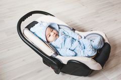 Portrait of cute mixed race baby boy sitting in car seat. Child transportation safety Stock Photo