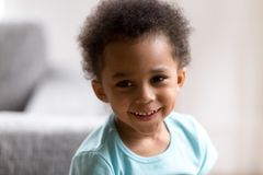 Portrait of cute mixed race toddler boy smiling. Portrait of funny little mixed race toddler boy smiling playing at home posing for picture, cute small African royalty free stock images