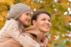 Portrait of cute mother and daughter hugging outdoors stock image