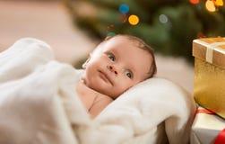 Portrait of cute newborn baby lying under beige blanket Royalty Free Stock Image