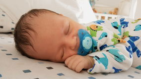 Portrait of cute newborn baby with soother sleeping in bed stock video