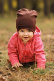 Portrait of a cute one year old girl crawling in the spring park Stock Photos
