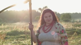 Portrait cute overweight woman holding a scythe looking at camera on the green summer field in sunlight. Beautiful. Landscape. Folklore, traditions concept stock video footage