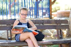 Portrait of cute pensive little girl with glasses sitting on the wooden bench with open book in hands outdoors. royalty free stock image