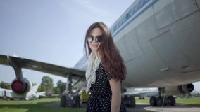 Portrait cute playful brunette girl wearing sunglasses in front of the big plane and looking at camera. Summertime. joy stock video footage
