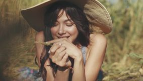 Portrait of a cute and playful smiling young girl in a straw hat in a wheat field. The girl lies on the grass stock footage