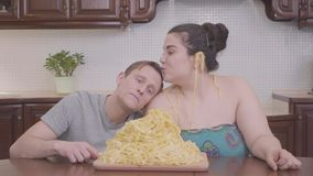 Portrait cute plump woman and skinny blond man in the kitchen at the table in front of big plate with noodles. The man stock video footage