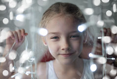 Portrait of a cute preschool girl with a radiant garland of lights in her hands. Stock Photography