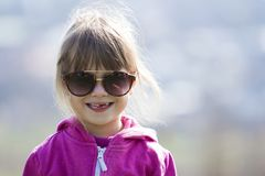 Portrait of cute pretty little blond preschool girl in pink sweater and dark sunglasses smiling happily in camera with funny child royalty free stock photography