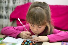 Portrait of cute pretty little serious child girl drawing with pencil on paper on blurred background. Art education, creativity, stock image