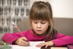 Portrait of cute pretty little serious child girl drawing with pencil on paper on blurred background. Art education, creativity, royalty free stock photos