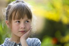 Portrait of cute pretty thoughtful child girl outdoors on blurred sunny colorful bright background.  royalty free stock image