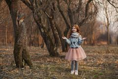 Portrait of a cute red-haired girl with freckles standing in an autumn or spring park or forest royalty free stock images
