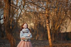 Portrait of a cute red-haired girl with freckles standing in an autumn or spring park or forest. Inspiration and dreams royalty free stock images