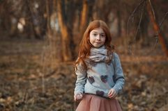 Portrait of a cute red-haired girl with freckles standing in an autumn or spring park or forest royalty free stock photo