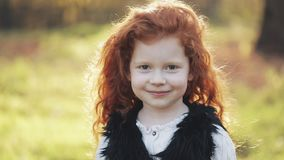Portrait of cute redhead little girl in an autumn park. Slow motion. Autumn park. Young little girl is smiling at the stock video