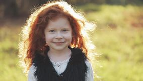 Portrait of cute redhead little girl walking in an autumn park. Slow motion. Autumn Park. Young little girl is smiling stock footage