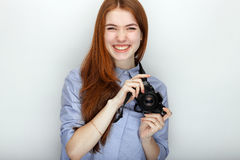 Portrait of cute redhead photographer woman wearing blue striped shirt smiling with happiness and joy while posing with camera aga Royalty Free Stock Photo