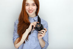 Portrait of cute redhead photographer woman wearing blue striped shirt smiling with happiness and joy while posing with camera aga Stock Image