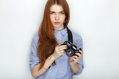 Portrait of cute redhead photographer woman wearing blue striped shirt smiling with happiness and joy while posing with camera aga Stock Photos