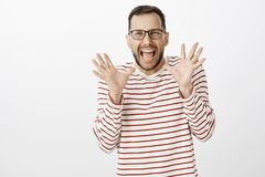 Portrait of cute scared adult gay boyfriend in glasses, screaming from fear and holding palms raised near face, seeing. Something shocking and terrifying stock photography