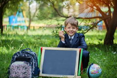 Portrait of cute school boy in the park, sunny day royalty free stock photos
