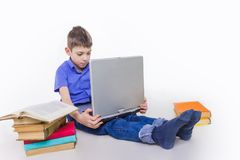 Portrait of cute schoolboy sitting with books and typing on laptop keyboard. Portrait of cute teen schoolboy sitting near books and typing on laptop keyboard Royalty Free Stock Image