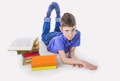 Portrait of cute schoolboy sitting with books and typing on laptop keyboard. Portrait of cute teen schoolboy sitting near books and typing on laptop keyboard Royalty Free Stock Images