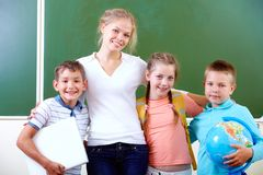 Teacher and schoolkids. Portrait of cute schoolchildren and teacher in classroom Royalty Free Stock Photo