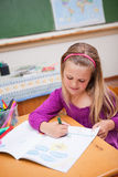 Portrait of a cute schoolgirl drawing royalty free stock photography