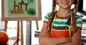 Portrait of cute schoolgirl standing with arms crossed at table 4k stock video