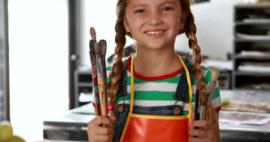 Portrait of cute schoolgirl standing with paintbrushes 4k stock video