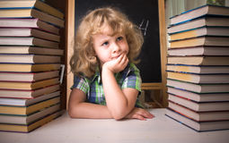 Portrait of cute schoolgirl thinking while sitting Royalty Free Stock Photo