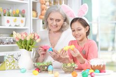 Portrait of cute senior grandmother and granddaughter. Senior grandmother and granddaughter with Easter eggs royalty free stock photo