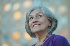 Portrait of cute senior woman in summer park stock photos