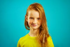 Portrait of cute seven years old girl with red hair and beautiful freckles, wears yellow t-shirt, expresses sincere stock photos