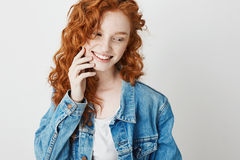 Portrait of cute shy redhead girl smiling looking in side over white background. Copy space. Stock Image