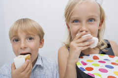 Portrait of cute siblings eating birthday cake slices in house Royalty Free Stock Image