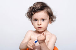 Portrait of a cute sick baby boy with fever holding a thermometer. Royalty Free Stock Photo