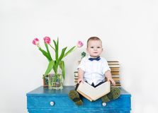 Portrait of the cute small boy sitting on a table with the book in hands. Childhood Stock Image